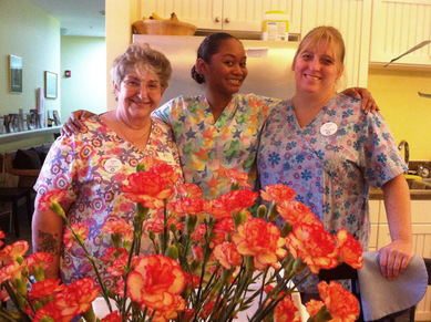 Smiling caregivers with flowers